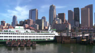 Stock Video Footage of The Seattle skyline from the harbor with ferry boats in foreground.