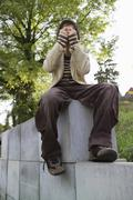 teenage boy (13-15) sitting on wall, face covered by hands - stock photo