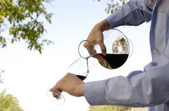 man pouring red wine in glass - stock photo