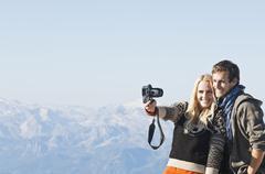 Austria, Steiermark, Dachstein, Young couple photographing on mountain, smiling - stock photo