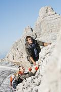 Austria, Steiermark, Dachstein, Young couple climbing rock - stock photo
