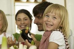 Parents with children (4-5) playing in kitchen, smiling Stock Photos