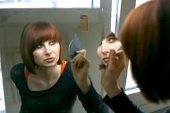 Woman looking into mirror, portrait Stock Photos