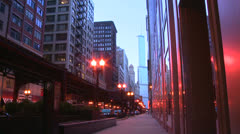 The El train passes on an elevated platform at dusk in downtown Chicago. Stock Footage