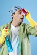 Man holding cleaning agent and cleaning cloth, hand on head, portrait Stock Photos