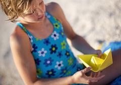Croatia, Zadar, Girl making paper boat Stock Photos