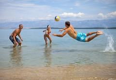 Croatia, Zadar, Friends playing volley ball at beach - stock photo