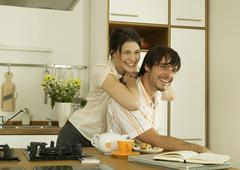 Young couple in kitchen, looking away, smiling Stock Photos