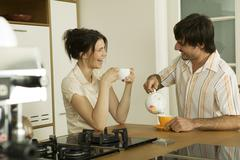 young couple in kitchen, drinking tea, smiling - stock photo