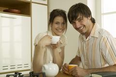 Young couple drinking tea in kitchen, smiling, portrait Stock Photos