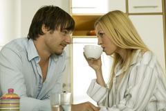 Young couple having breakfast in kitchen Stock Photos