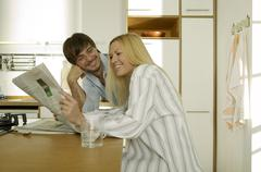 young couple in kitchen, man looking at woman reading newspaper, smiling - stock photo