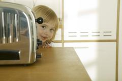 Girl (4-5) behind toaster in kitchen, close-up, portrait Stock Photos