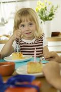 little girl (4-5) eating birthday cake with friend - stock photo