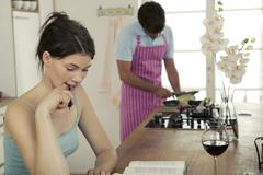 Woman working in kitchen, man cooking Stock Photos