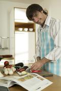 Young man cutting vegetables in kitchen, portrait, close-up Stock Photos