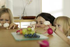 Mother with children (4-5) in kitchen, (focus on background) Stock Photos