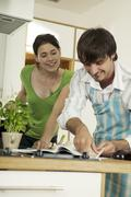 Young couple looking at recipe book in kitchen, smiling Stock Photos