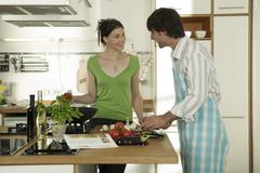 Stock Photo of young couple cooking food in kitchen, smiling