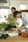 Young couple in kitchen, man cutting vegetables Stock Photos
