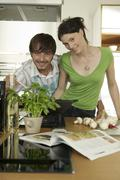 Stock Photo of young couple cooking food in kitchen, portrait, smiling
