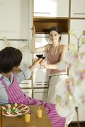 young couple toasting wine glasses in kitchen, woman smiling - stock photo