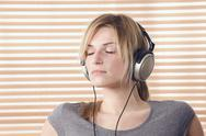 Stock Photo of Blonde wearing headphones, eyes closed, portrait