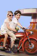 Germany, Landshut, boy and girl (4-5) riding carousel bike - stock photo