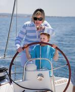 Croatia, Zadar, Mother and son steering wheel on sail boat - stock photo