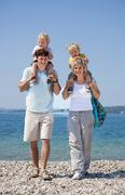 Croatia, Zadar, Parents carrying children on shoulder at beach Stock Photos