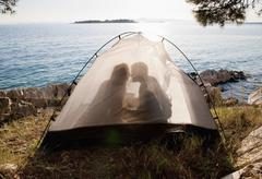 Croatia, Zadar, Young couple kissing in tent at beach - stock photo