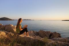 Croatia, Zadar, Young woman with book looking at view from beach Stock Photos