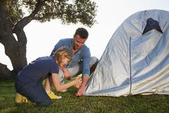 Croatia, Zadar, Father and daughter putting up tent - stock photo