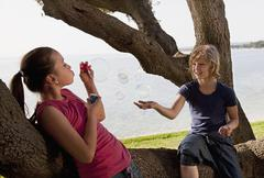Croatia, Zadar, Girls sitting on tree trunk and blowing bubble Stock Photos