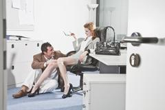 Germany, Business people in office, Business man touching woman's knee Stock Photos
