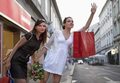 Croatia, Zagreb, Young women on street hailing for taxi - stock photo