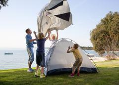 Croatia, Zadar, Family putting up tent at beach - stock photo