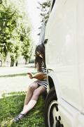 Germany, Cologne, Young woman sitting in bus and reading book - stock photo