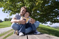 Stock Photo of father and son (4-7) sitting on bench, portrait