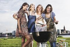 Stock Photo of Germany, Cologne, Woman preparing while friends watching