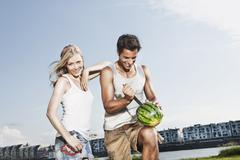 Stock Photo of Germany, Cologne, Man cutting watermelon, woman smiling