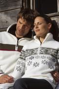 Stock Photo of Germany, Bavaria, Couple sitting outside lodge, close-up