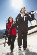 Italy, Alto Adige, Couple carrying ski, looking away Stock Photos