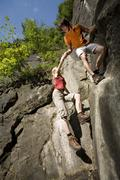 young couple rock climbing, low angle view - stock photo
