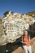 Stock Photo of Italy, Liguria, Riomaggiore, Woman sitting on stone wall
