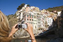 Italy, Liguria, Riomaggiore, Woman photographing houses - stock photo