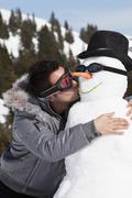 Germany, Bavaria, Man kissing snowman, close up Stock Photos