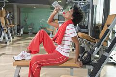 Germany, Bavaria, Woman drinking water in gym, side view, portrait - stock photo