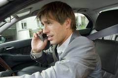Businessman using mobile phone in car, side view, close-up Stock Photos