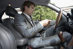 Young man with mobile phone, sitting in car Stock Photos